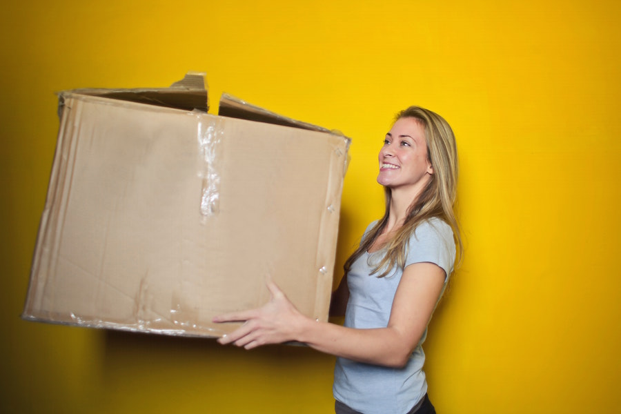 A woman carrying a box.