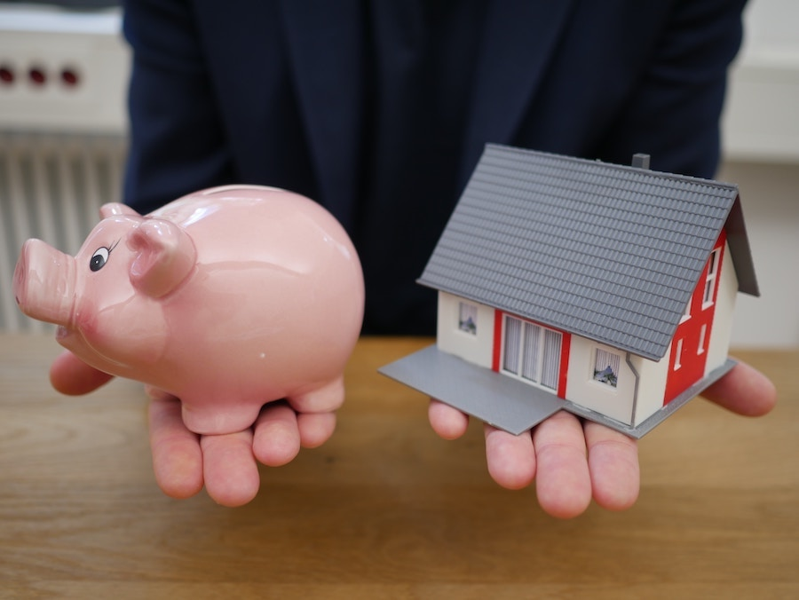 Millennial buyers holding a house and piggy bank